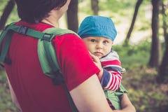 Engendre detener a su hijo en el portador de bebé que camina en el parque Fotografía de archivo libre de regalías