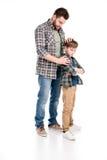 Engendre el abarcamiento del hijo serio que se coloca con los brazos cruzados Fotografía de archivo