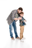 Engendre el abarcamiento del hijo serio que se coloca con los brazos cruzados Imagenes de archivo