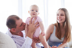 Engendre el abarcamiento y besar a su pequeña hija mientras que lo de la madre Imagen de archivo