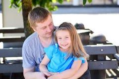Engendre el abrazo de la hija en el banco en el parque en día de verano soleado Fotografía de archivo