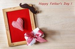 Engendre el corazón del fondo del día del ` s en un marco en un fondo rojo, con una caja de regalo y un bigote negro Espacio libr Imagen de archivo libre de regalías