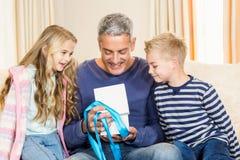 Engendre el regalo de la abertura dado por los niños en el sofá Fotos de archivo libres de regalías