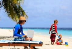 Engendre el trabajo en el ordenador portátil mientras que los niños juegan en la playa Imagenes de archivo