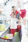 Engendre empujar a la hija joven en carretilla de las compras con los bolsos de compras Imágenes de archivo libres de regalías