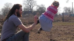Engendre empujar a su hija en el oscilación mientras que divirtiéndose en el parque metrajes