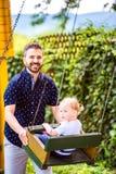 Engendre empujar a su hija en el oscilación en un parque Foto de archivo