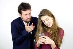 Engendre enojado con la hija que juega con el teléfono elegante Imagenes de archivo