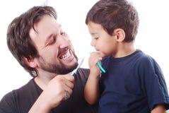 Engendre enseñando a su hijo a cómo limpiar los dientes imagen de archivo libre de regalías