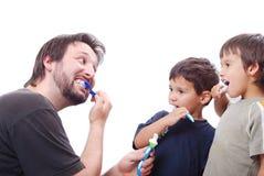 Engendre enseñando a sus dos hijos a cómo limpiar los dientes Fotografía de archivo