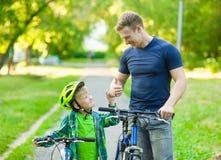 Engendre hablar con su hijo que monta una bicicleta y que muestra el pulgar para arriba fotos de archivo
