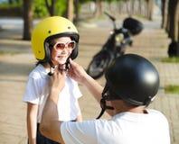 Engendre intentar llevar un casco de la bici a su hija fotos de archivo