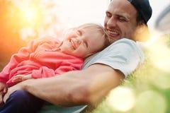 Engendre jugar con la hija sonriente en el parque en el día soleado imagenes de archivo