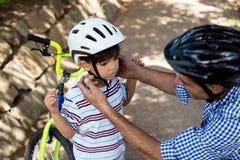 Engendre la ayuda del hijo en casco de la bicicleta que lleva en parque Imagenes de archivo