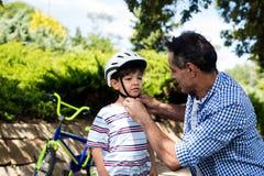 Engendre la ayuda del hijo en casco de la bicicleta que lleva en parque Fotos de archivo