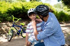 Engendre la ayuda del hijo en casco de la bicicleta que lleva en parque Fotografía de archivo