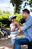 Engendre la ayuda del hijo en casco de la bicicleta que lleva en parque Imagen de archivo