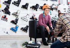 Engendre la ayuda a su niño levantarse en los nuevos rodillos Foto de archivo libre de regalías