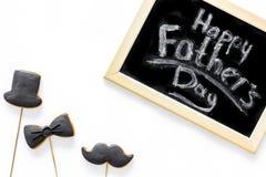 Engendre la celebración del día o del cumpleaños del ` s con las galletas de la muestra del lazo negro, del bigote y del sombrero Imagen de archivo libre de regalías