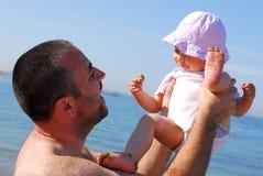 Engendre la elevación de su hija del bebé en la playa Fotos de archivo