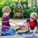 Engendre la enseñanza de dos muchachos del niño reparar la cadena en las bicis Fotos de archivo