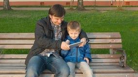 Engendre la enseñanza de su hijo joven lindo utilizar una tableta almacen de metraje de vídeo