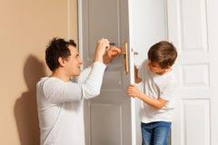 Engendre la enseñanza de su hijo reparar el tirador de puerta Foto de archivo