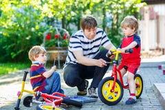 Engendre la enseñanza de sus pequeños hijos reparar las bicis Foto de archivo libre de regalías