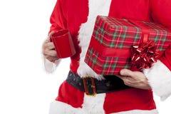 Engendre la Navidad que lleva un presente arqueado rojo y que come una taza de té Fotos de archivo libres de regalías