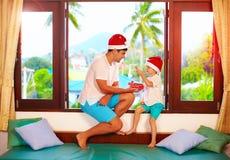 Engendre la presentación hijo de los caramelos sabrosos en la Navidad, mientras que se sienta en alféizar en las zonas tropicales Imagen de archivo