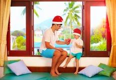 Engendre la presentación hijo de los caramelos sabrosos en la Navidad, mientras que se sienta en alféizar en las zonas tropicales Imagen de archivo libre de regalías