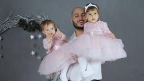Engendre la relación de las hijas, papá contento que presenta para la foto con los niños en los brazos en estudio en fondo de la  metrajes