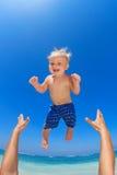 Engendre lanzar para arriba en el aire a un niño feliz Foto de archivo