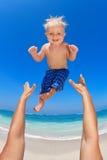 Engendre lanzar para arriba en el aire a un niño feliz Fotografía de archivo