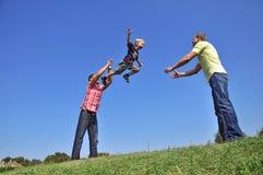 Engendre lanzar a su hijo en el aire y la cogida hola Fotografía de archivo libre de regalías