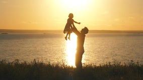 Engendre lanzar a su niño para arriba en el aire en la playa en la puesta del sol almacen de metraje de vídeo