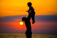 Engendre lanzar a su niño para arriba en el aire en la playa, tiro de la silueta Fotos de archivo libres de regalías