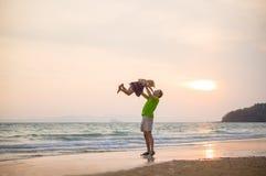 Engendre levantan para arriba a la hija en las manos en la playa del océano de la puesta del sol con el yach Fotos de archivo libres de regalías