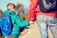 Engendre llevar a cabo la mano del pequeño hijo con la mochila en el camino Imagenes de archivo
