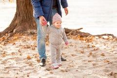 Engendre llevar a cabo las manos con la pequeña hija en la playa Foto de archivo libre de regalías