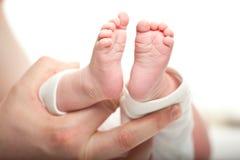 Engendre llevar a cabo los pies de su bebé recién nacido Foto de archivo
