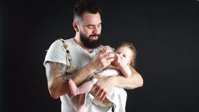 Engendre llevar a cabo y tomar el cuidado del pequeño bebé infantil, alimentando desde la botella almacen de metraje de vídeo