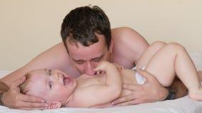 Engendre los besos y las cosquillas su pequeño hijo Ponen en la cama después de dormir El bebé es menos de dos años almacen de video