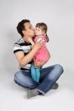 Engendre los controles y los besos su hija Fotos de archivo