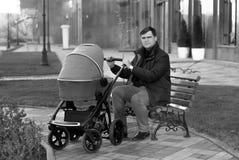 Engendre sentarse en banco en el parque con el cochecito de bebé Imágenes de archivo libres de regalías