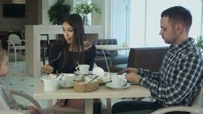 Engendre usando su ordenador portátil mientras que se sienta con su esposa e hija en café Comprensión de la mujer y no molestarlo almacen de metraje de vídeo