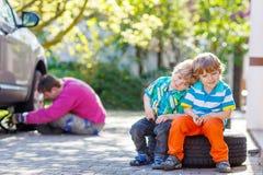 Engendre y dos muchachos del niño que reparan el coche y la rueda de cambio Foto de archivo libre de regalías