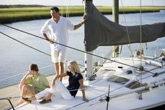 Engendre y dos niños adolescentes que se relajan en el barco Fotos de archivo