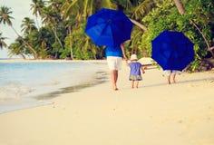 Engendre y dos niños en la playa con los paraguas Fotografía de archivo