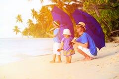 Engendre y dos niños en la playa con los paraguas Foto de archivo
